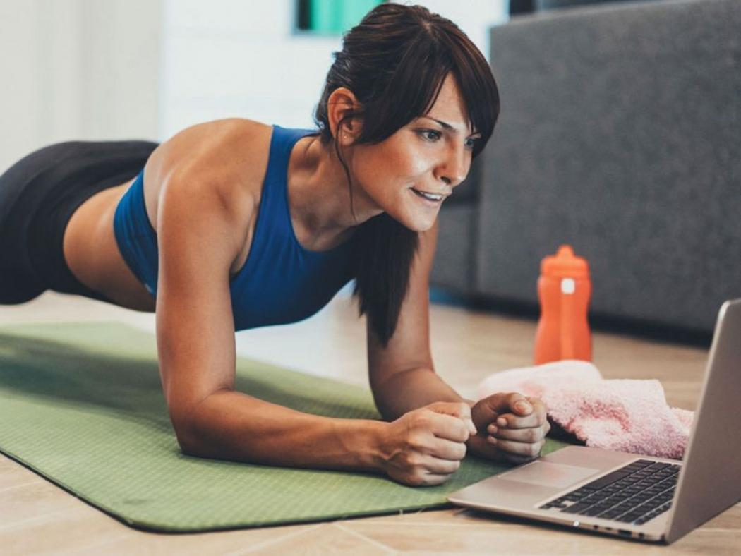 Woman doing a plank while using ACC Sweat On Demand workout videos on laptop.