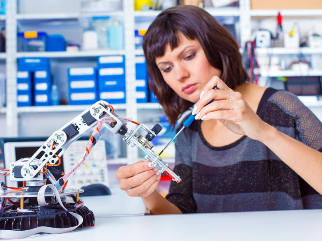 Woman working with robotic arm.