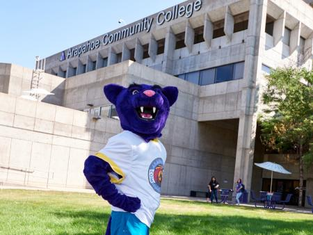 Arapahoe Community College Puma mascot poses outside of the main building on the Littleton Campus