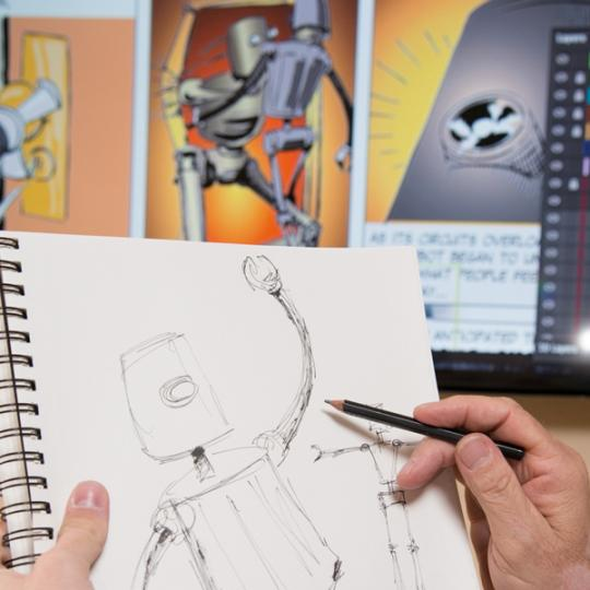 A student is working on a drawing of a robot, holding a pencil and sketch pad up to a computer to compare their graphic design to a completed and colored illustration.