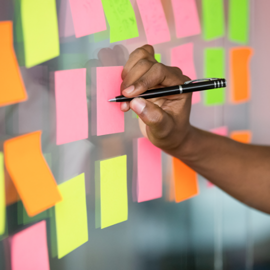 person writing on sticky notes on wall